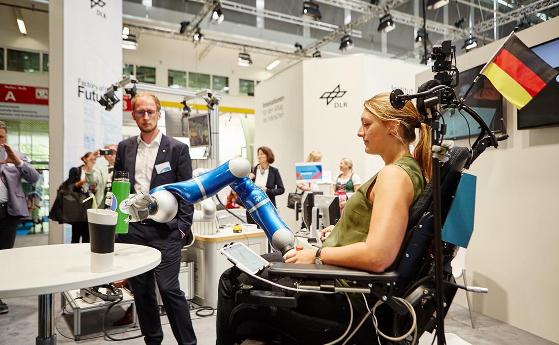 Am Messestand des DLR zeigen sich Einsatzmöglichkeiten für Roboterarme im Gesundheitswesen.